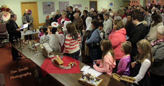 Bishop Marcel Damphousse blessing Nativity Scenes for use in area homes