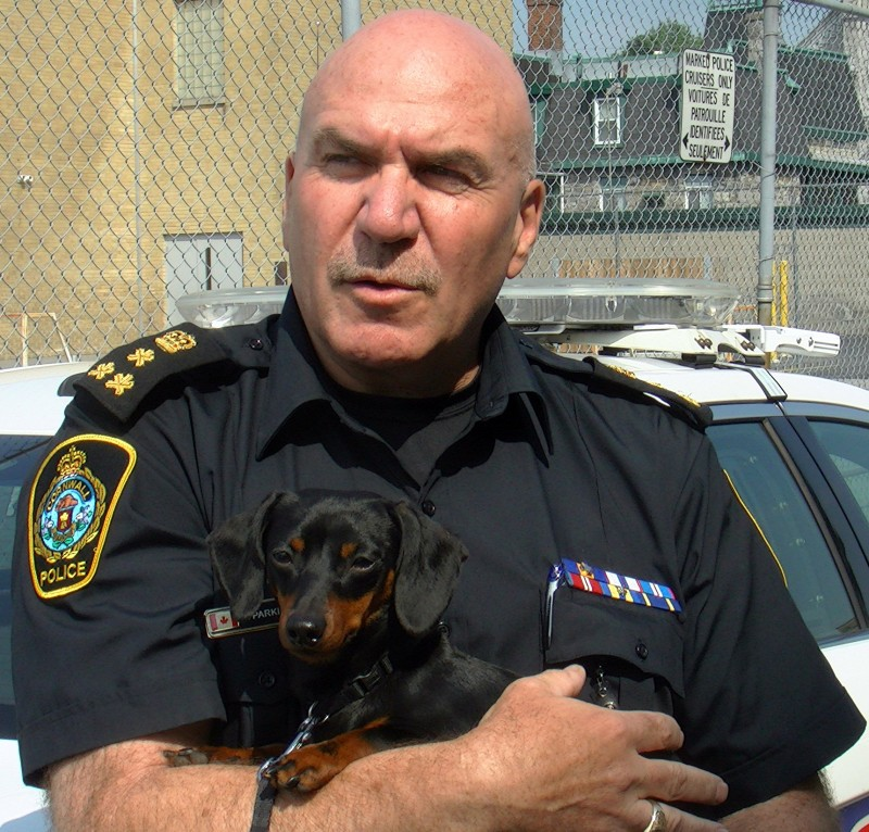 Cornwall Ontario Police Chief Dan Parkinson holding Fitzy the Dachshund.